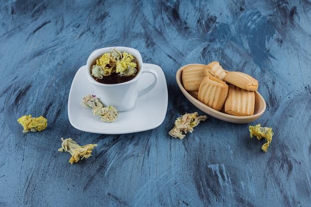Köstliche kekse mit einer tasse kräutertee auf blauer oberfläche.
