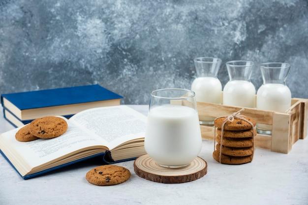 Köstliche kekse mit glas milch und buch.