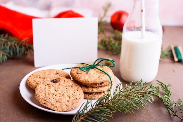 Köstliche kekse mit schokolade auf einem weißen teller, milch, weihnachtsmütze, verspotten für text. brief und kekse für den weihnachtsmann.