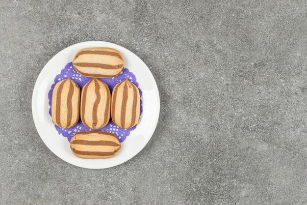 Köstliche kekse mit schokoladenstreifen auf weißem teller