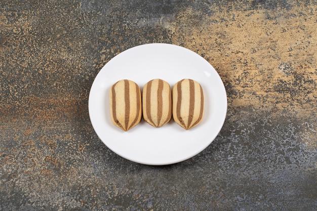 Köstliche kekse mit schokoladenstreifen auf weißem teller.