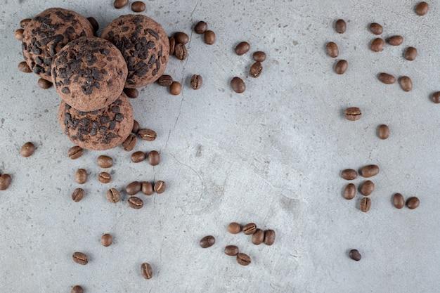 Köstliche kekse mit schokoladenstückchen und verstreuten kaffeebohnen auf marmoroberfläche