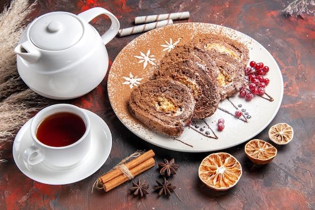 Köstliche keksröllchen mit halber draufsicht mit einer tasse tee auf einem süßen kuchen mit dunklem tisch