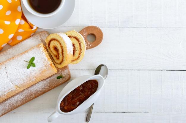 Köstliche keksrolle mit aprikosenmarmelade und einer tasse tee auf einem weißen holztisch.