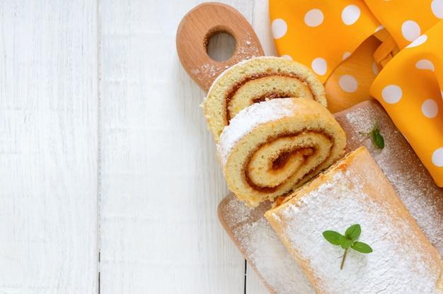 Köstliche keksrolle mit aprikosenmarmelade und puderzucker auf einem weißen holztisch.