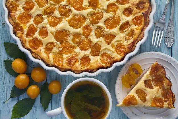 Köstliche kirschpflaumenpastete in einer auflaufform auf einem blau gestrichenen holztisch, umgeben von kirschpflaumenbeeren und minzkräutertee. herbsternte im garten