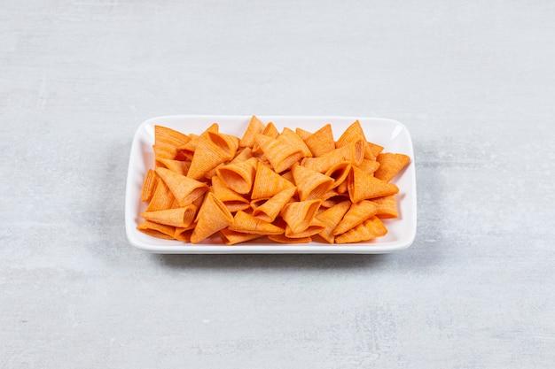 Köstliche knusprige chips auf weißem teller.