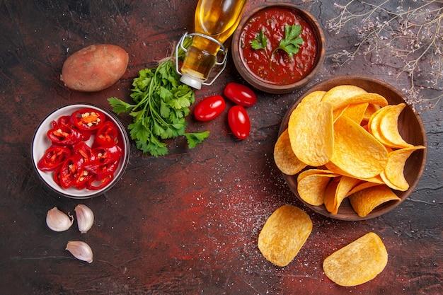Köstliche knusprige kartoffelchips in einer kleinen braunen schüssel gefallene ölflasche grüne tomaten knoblauchketchup gehackter pfeffer auf dunklem tisch