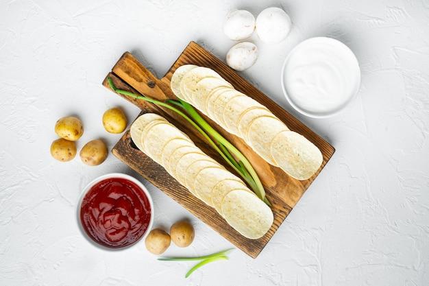 Köstliche knusprige kartoffelchips mit dip-saucen, tomatendip-sauerrahm, auf weißem stein