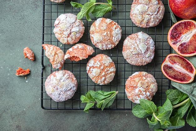 Köstliche, knusprige orangen-crinkle-kekse mit zitrusfrüchten und puderzucker auf schwarzem metallgitter, grüne betonoberfläche