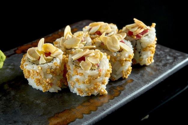 Köstliche knusprige sushi-rolle mit thunfisch, erdnüssen, popcorn und gurke, serviert auf einem keramikteller mit ingwer und wasabi.