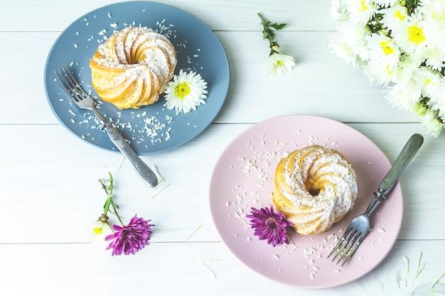 Köstliche kuchen mit kokosnusschips auf rosa und grauer platte auf weißer tabelle