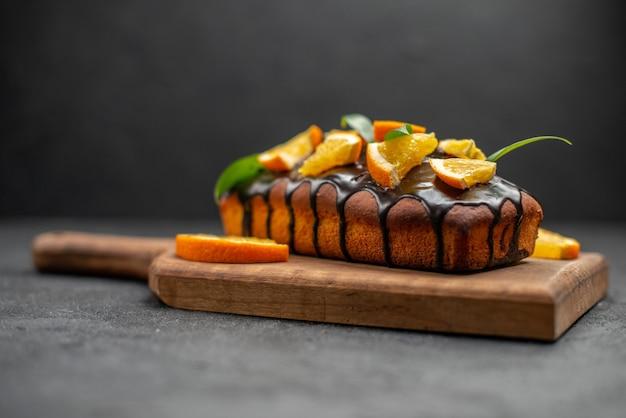 Köstliche kuchen verziert mit orange und schokolade auf hölzernem schneidebrett auf schwarzem tisch