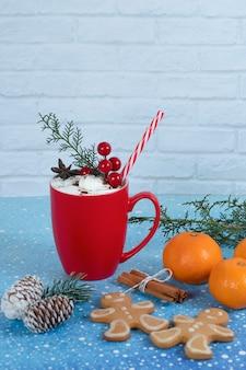 Köstliche lebkuchenplätzchen, tangeriens und rote tasse kaffee auf blauem hintergrund. hochwertiges foto