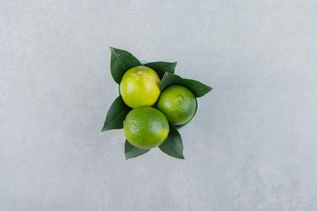 Köstliche limettenfrüchte in blauer schüssel.