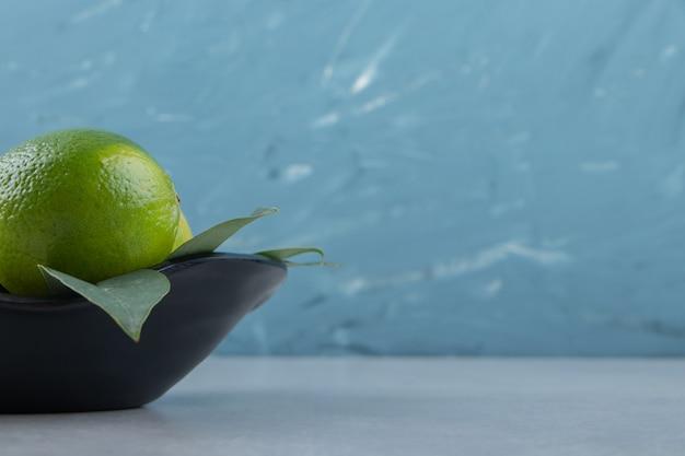 Köstliche limettenfrüchte in schwarzer schüssel.