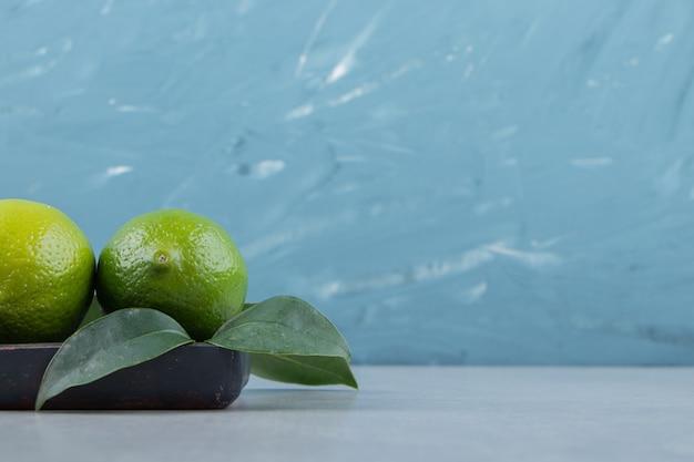 Köstliche limettenfrüchte mit blättern auf schwarzem teller.