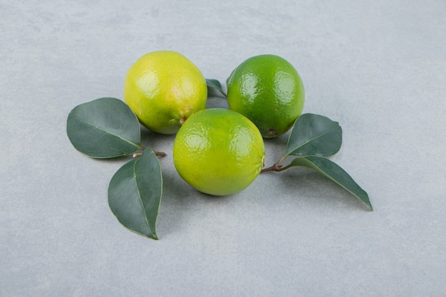 Köstliche limettenfrüchte mit blättern auf steintisch.