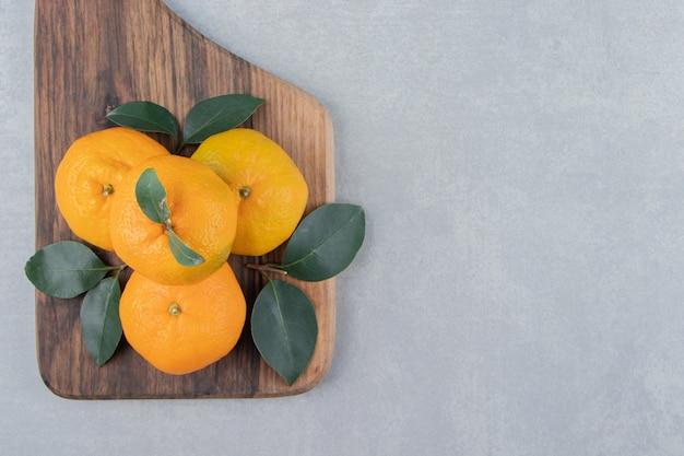 Köstliche mandarinenfrüchte auf holzbrett.