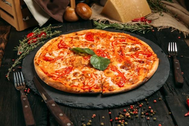 Köstliche margarita-pizza mit tomate und käse auf der tafel auf dem dunklen holztisch mit kräutern und tomaten