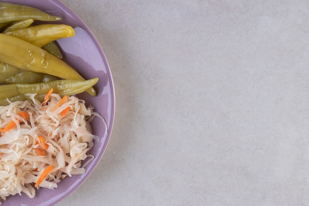 Köstliche marinierte paprika und sauerkraut auf lila teller.