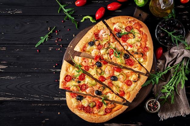 Köstliche meeresfrüchtegarnelen- und -miesmuschelpizza auf einem schwarzen holztisch.
