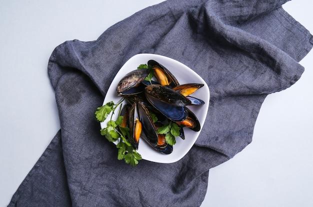 Köstliche miesmuscheln auf blauer tischdecke