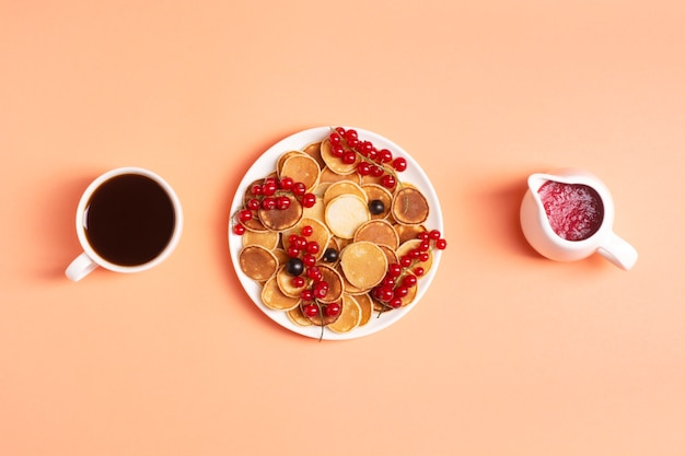 Köstliche minitaschen in einem weißen teller mit roten und schwarzen johannisbeeren auf einem pfirsich