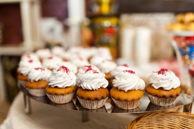 Köstliche muffins mit weißer sahnehochzeitstafel für gäste.
