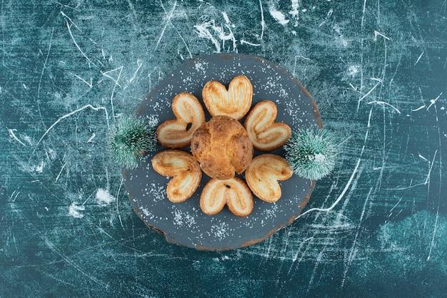 Köstliche muffins und kekse auf einem dunklen holzbrett. foto in hoher qualität