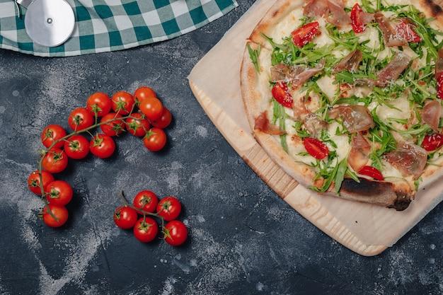 Köstliche neapolitanische pizza an bord mit kirschtomaten, freier platz für text