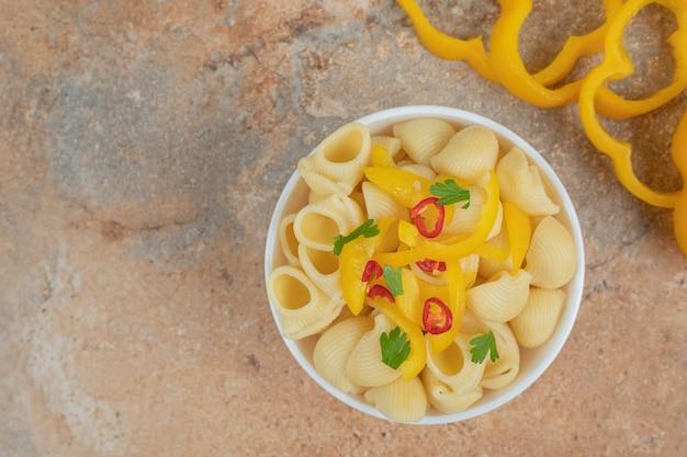 Köstliche nudel-pfeffer-scheiben auf orangefarbenem hintergrund