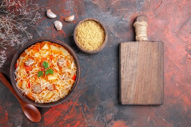 Köstliche nudelsuppe mit hühnchen und ungekochter pasta in einer kleinen braunen schüssel und löffel knoblauch neben dem schneidebrett auf dunklem hintergrund