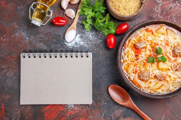 Köstliche nudelsuppe mit hühnchen und ungekochter pasta in einer kleinen schüssel und löffel knoblauch-tomaten-grün und notizbuch auf dunklem hintergrund