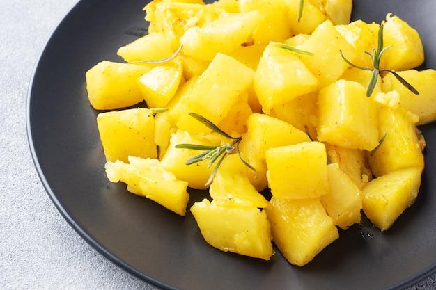 Köstliche ofenkartoffeln mit gewürzen, käse und rosmarin auf einem teller, nahaufnahme.