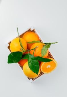 Köstliche orangen in einer holzkiste mit zweig draufsicht