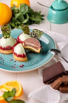 Köstliche orangen- und schokoladenkuchen in der spiegelminzglasur auf einem blauen teller auf einem weißen holztisch in der bäckerei