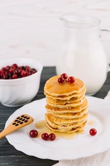 Köstliche pfannkuchen mit beeren des honigs und der roten johannisbeere auf weißer platte