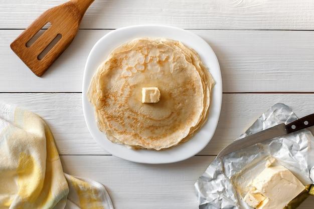 Köstliche pfannkuchen mit butter, die auf einer hölzernen tischoberansicht liegen