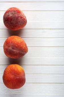 Köstliche pfirsiche auf einem weißen hölzernen hintergrund.