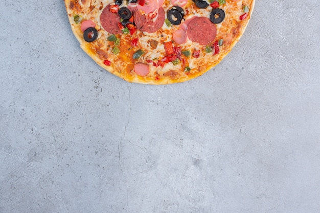 Köstliche pizza angezeigt auf marmorhintergrund.