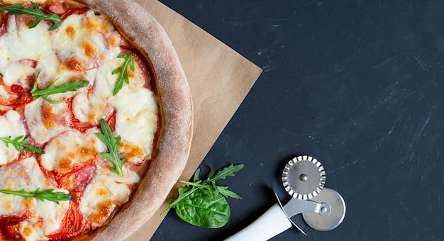 Köstliche pizza auf dunklem hintergrund und pizzaschneider und grüns mit kopierraum