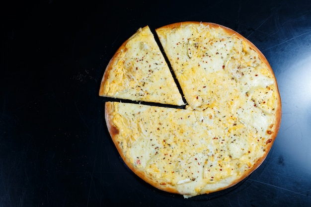 Köstliche pizza mit vier käsesorten mit cheddar, parmesan, mozzarella und tomatensauce auf schwarzem hintergrund. sicht von oben.