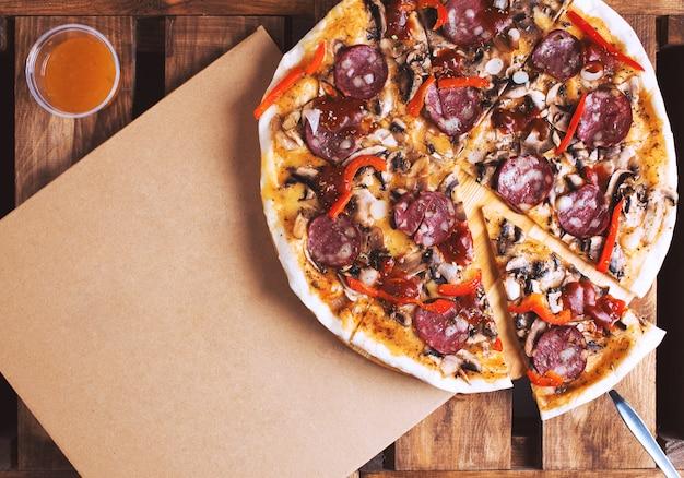 Köstliche pizza und karton lieferbox flach liegen