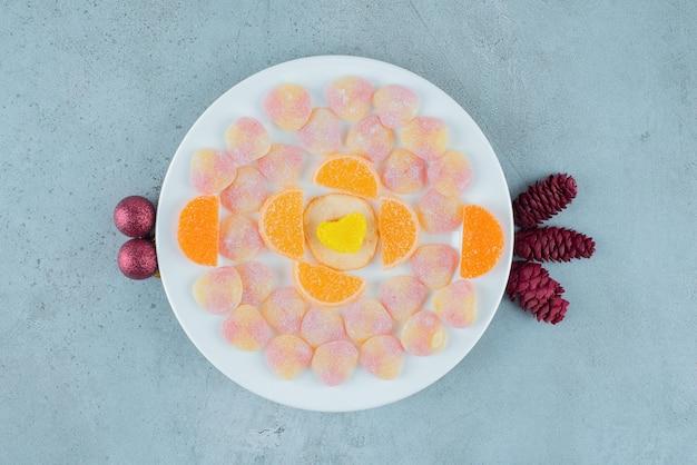 Köstliche platte mit verschiedenen marmeladen, mit tannenzapfen und kugeln auf marmor.