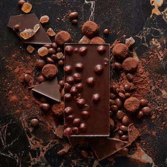 Köstliche praline und süßigkeiten mit kakaopulver auf dunkler marmoroberfläche