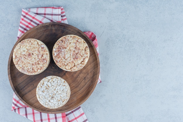 Köstliche puffreiskuchen auf tablett auf handtuch auf marmor.