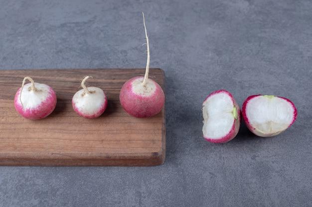 Köstliche radieschen mit brett, auf der marmoroberfläche.