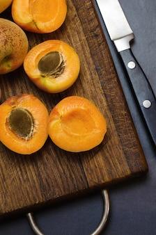 Köstliche reife aprikosen auf hölzernem schneidebrett