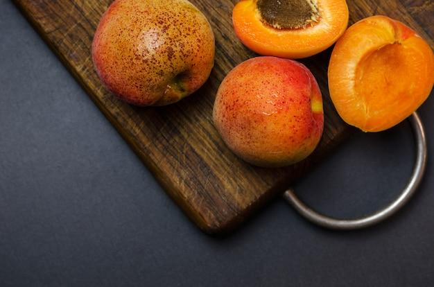 Köstliche reife aprikosen auf hölzernem schneidebrett.